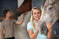 Woman stroking her horse young women Royalty Free Stock Photography