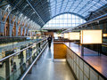 Woman strolling walkway on second level of st panc in middle distance strolls pancras arched glass ceiling the station overhead Royalty Free Stock Photos