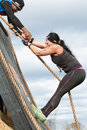 Woman struggles climbing wall in extreme obstacle course race buford ga usa november a to climb up a using a rope at the muddy Royalty Free Stock Photography
