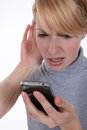 Woman struggling to hear her phone Stock Photography