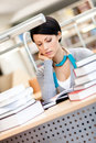 Woman studies at the library surrounded with piles of books reads sitting desk Royalty Free Stock Photos