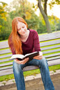 A woman studying the bible happy young christian reading in park Stock Photo
