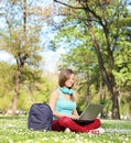 Woman studying with laptop seated on grass in park shot tilt and shift lens Royalty Free Stock Photo