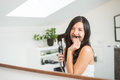 Woman styling her hair making a pretense moustache playful young with one of long tresses as she grins at herself in the Royalty Free Stock Photo