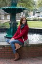 Woman in a stylish red coat brunette haired front fountain Royalty Free Stock Photo