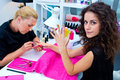 Woman with stylist on manicure treatment in beauty salon Stock Photos