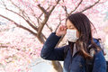 Woman suffer from pollen allergy under sakura tree at outdoor Royalty Free Stock Photo