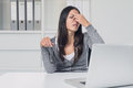Woman suffering from eye strain at her laptop young removing eyeglasses to rub eyes with finger with a pained Stock Photography
