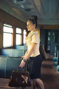 Woman with a suitcase walking in the retro train wagon Stock Photos