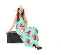 Woman in summer dress with hat and money sitting on a black case over white background Royalty Free Stock Images