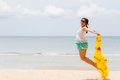 Woman in summer dress jumping over sand by tropical sea Royalty Free Stock Photo