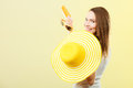 Woman in summer hat holds sunglasses sunscreen lotion holidays fashion and skin care concept yellow heart shaped bright background Stock Photography