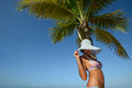 Woman in summer hat sunbathing under a palm tree on a background Royalty Free Stock Photos
