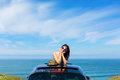 Woman on summer travel leaning out sunroof relaxed tranquil vacation to the coast car with the sea background Stock Photos