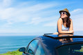Woman on summer vacation leaning out sunroof relaxed happy travel to the coast car with the sea background Royalty Free Stock Photos