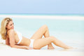 Woman sunbathing on beautiful beach holiday smiling Royalty Free Stock Image