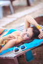 Woman sunbathing in bikini at tropical travel resort beautiful young woman lying on sun lounger near pool portrait of summer Royalty Free Stock Photo