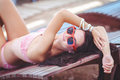 Woman sunbathing in bikini at tropical travel resort beautiful young woman lying on sun lounger near pool portrait of summer Stock Image