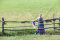 Woman in sundress standing near village fence in field copyspace Royalty Free Stock Image