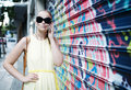 Woman in sunglasses chatting on a mobile phone while standing alongside wall covered colourful graffiti or mural Royalty Free Stock Photos