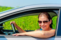 Woman in sunglasses driving a modern car Royalty Free Stock Images