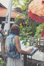 Woman in sunglasses with fashion snakeskin python bag near the restaurant. Bali island, Indonesia. Royalty Free Stock Photo