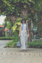Woman in sunglasses with fashion snakeskin python bag walking on the street. Bali island, Indonesia. Royalty Free Stock Photo