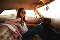 Woman in sunglasses resting while sitting inside a retro car Royalty Free Stock Photo