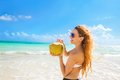 Woman with sunglasses on tropical beach enjoying ocean view beautiful a sea taking deep breath drinking coconut water Stock Photography