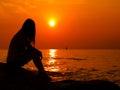 Woman sunset beach a alone watching the Stock Photo