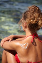 Woman with suntan lotion at the beach in form of a waves Stock Images