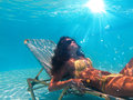 Woman suntanning underwater on a sunbed Stock Photo