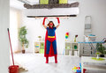 Woman in super hero costume holding bad in the air