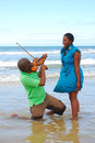 Woman surprised by beach musician a beautiful young african american in blue dress with smiling facial expression standing in the Royalty Free Stock Photos