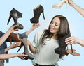 Woman surrounded by many shoes funny portrait of smiling fashion brunette with long hair elegant Royalty Free Stock Images