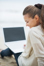 Woman in sweater sitting on lonely beach and using laptop happy young Royalty Free Stock Images