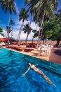 Žena plávanie plávajúce v bazén v tropický pobrežia stredisku na pláž