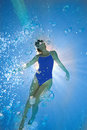 Woman in swimming pool underwater view lens flare Royalty Free Stock Images