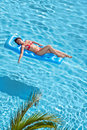 Woman in swimsuit bakes on inflatable mattress red pool Stock Photography