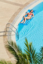 Woman in swimsuit bakes lying on inflatable mattress young red water near to edge of pool Stock Photography
