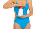 Woman in swimsuit holding bottle of cream closeup on young sun block creme Royalty Free Stock Image