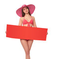 Woman in swimsuit holding red blank cardboard young pink bikini and summer hat over white background Royalty Free Stock Image