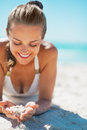 Woman in swimsuit laying on beach and playing with sand happy young Royalty Free Stock Photos