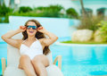 Woman in swimsuit relaxing on chaise-longue Royalty Free Stock Photo