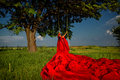 Woman in on the swing beautiful red dress with flower wreath forest sunset Royalty Free Stock Images