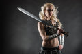 Woman and sword performer wearing sexy costume holding a grey smoky background Royalty Free Stock Image