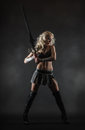 Woman and sword performer wearing sexy costume holding a grey smoky background Royalty Free Stock Photography