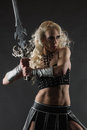 Woman and sword performer wearing sexy costume holding a grey smoky background Royalty Free Stock Images