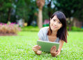 Woman with tablet computer lying on grass Stock Photos