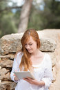 Woman with a tablet pc in the park beautiful young redhead leaning against an old stone wall as she scrolls using touchscreen Royalty Free Stock Image